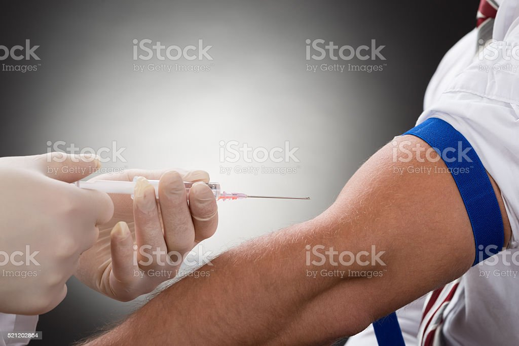 Doctor Injecting Syringe On Patient's Arm stock photo