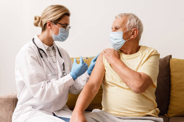 Doctor injecting vaccine to elderly man during home visit stock photo