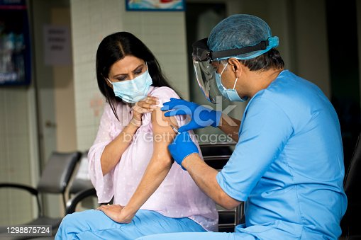 Doctor wearing protective workwear and injecting vaccine into arm of patient