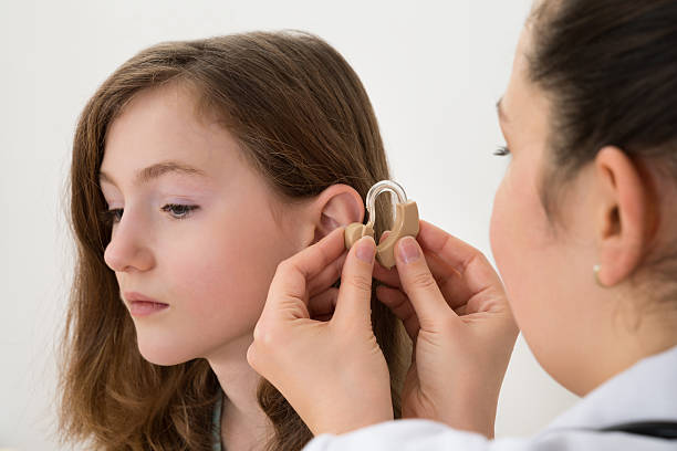 Doctor Inserting Hearing Aid In The Ear Of A Girl stock photo