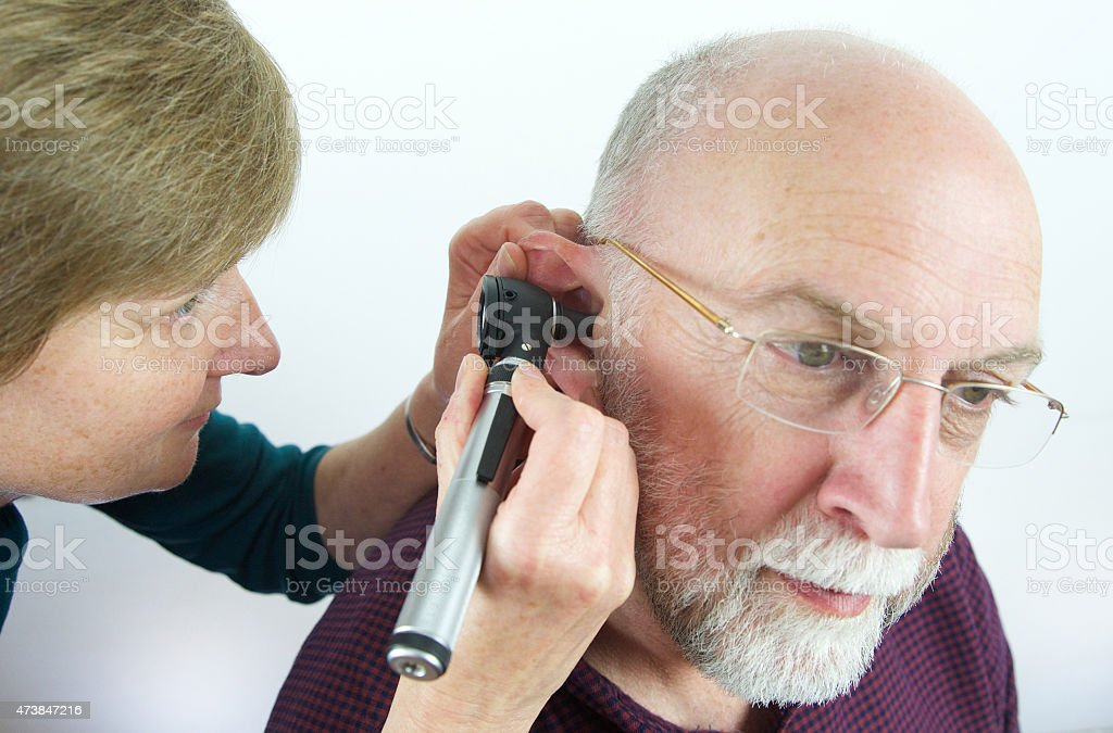 Doctor inspects patient's ear with an auroscope stock photo