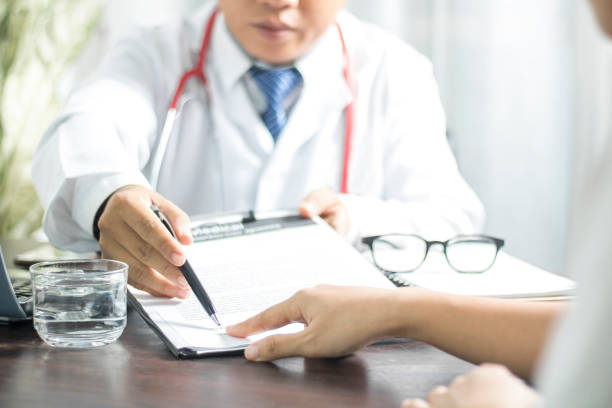 doctor introduces patient signing on medical records before treat illness in hospital - permit stock photos and pictures