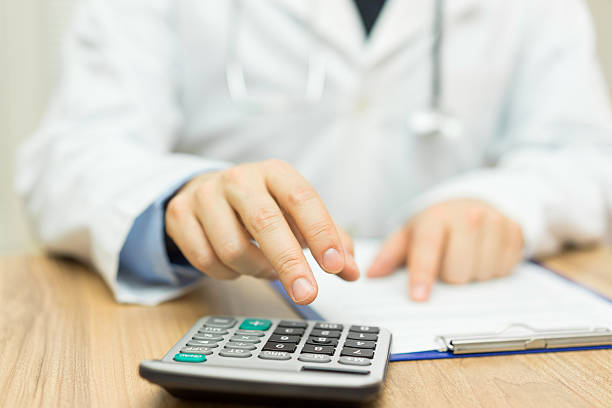 doctor is calculating cost of treatment stock photo
