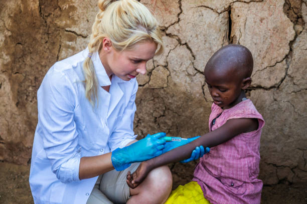 Doctor is doing an injection to little African girl in small village, Kenya stock photo