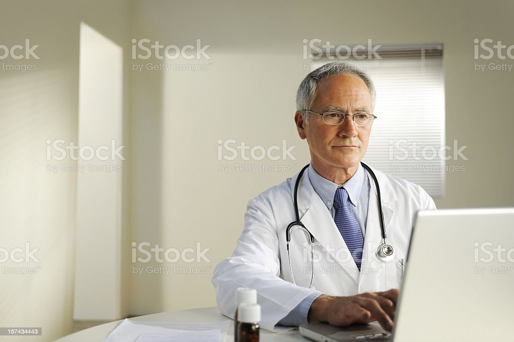 Doctor is engrossed in doing research on laptop stock photo