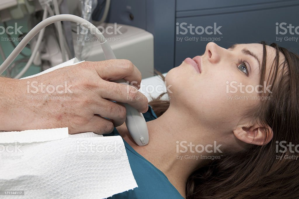 Doctor is giving beautiful young patient an ultra sound royalty-free stock photo