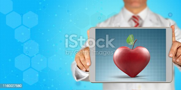A doctor holds a digital tablet and shows hearth shaped red apple for heart health message on screen in front of blue, hexagonal and technological background. With copy space.