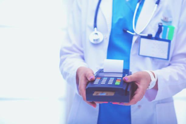 Arzt hält Bezahlterminal in Händen Zahlen für die Gesundheitsversorgung. Arzt – Foto