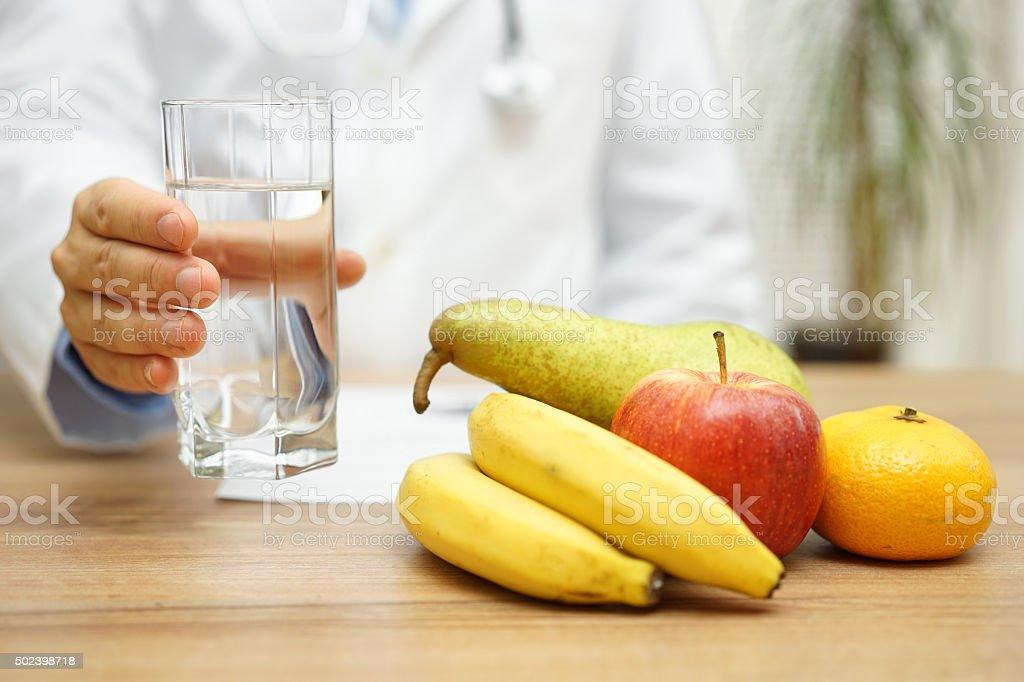 Arzt mit Wasser und frisches Obst nach reading diagnose. – Foto