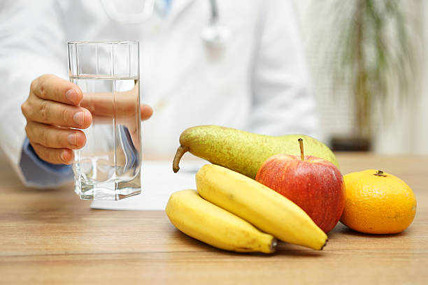 Doctor is offering water and fruit after reading diagnose. stock photo