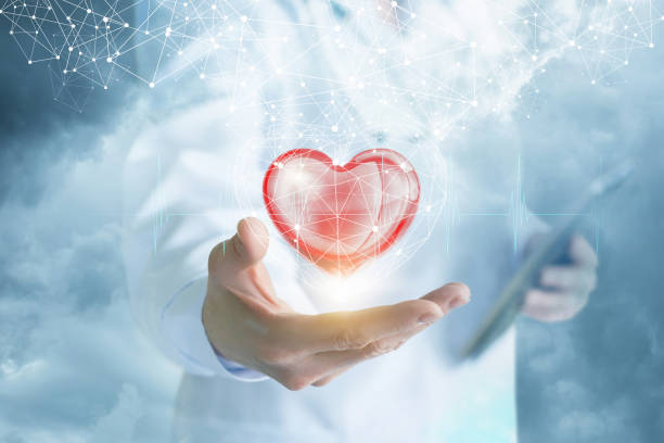 A doctor is showing a bright heart in the digital connections cage with a cloud of wireless connections above . stock photo