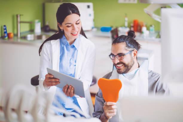 läkare visar medicinska rapporten till sin patient - two dentists talking bildbanksfoton och bilder