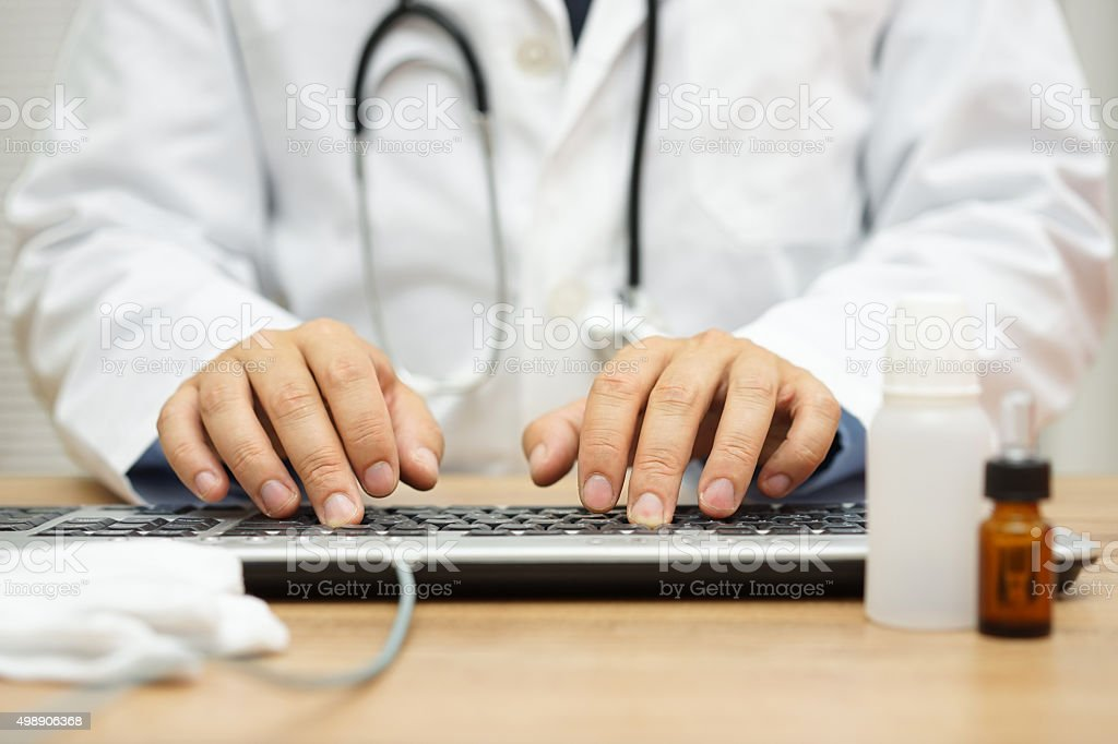 Doctor is typing diagnose on computer keyboard stock photo