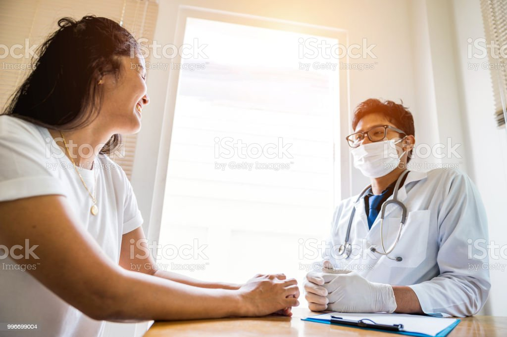 A doctor is working in the hospital, he is wearing a brown stethoscope and he is investigating the illness of the patient. stock photo