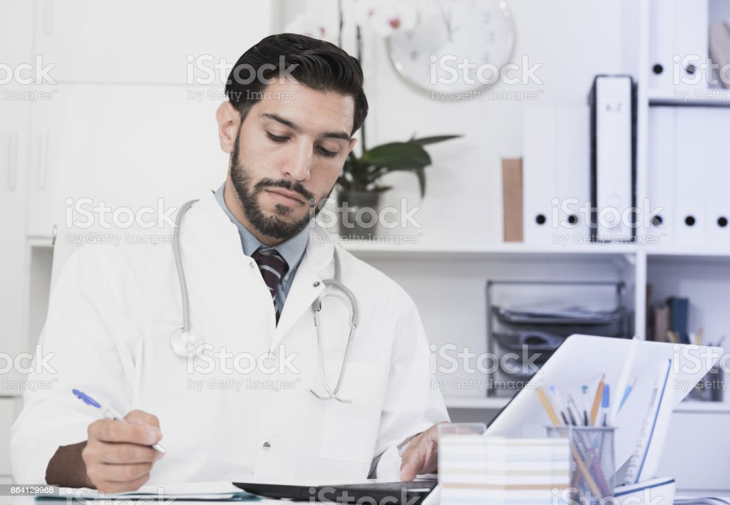 Doctor is working with documents in laptop royalty-free stock photo