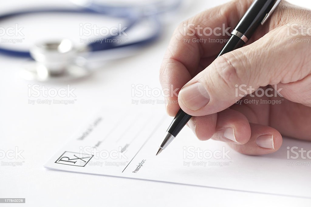 Doctor is Writing a Prescription in the Consulting Room stock photo