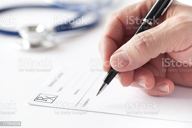 Doctor Is Writing A Prescription In The Consulting Room Stock Photo - Download Image Now
