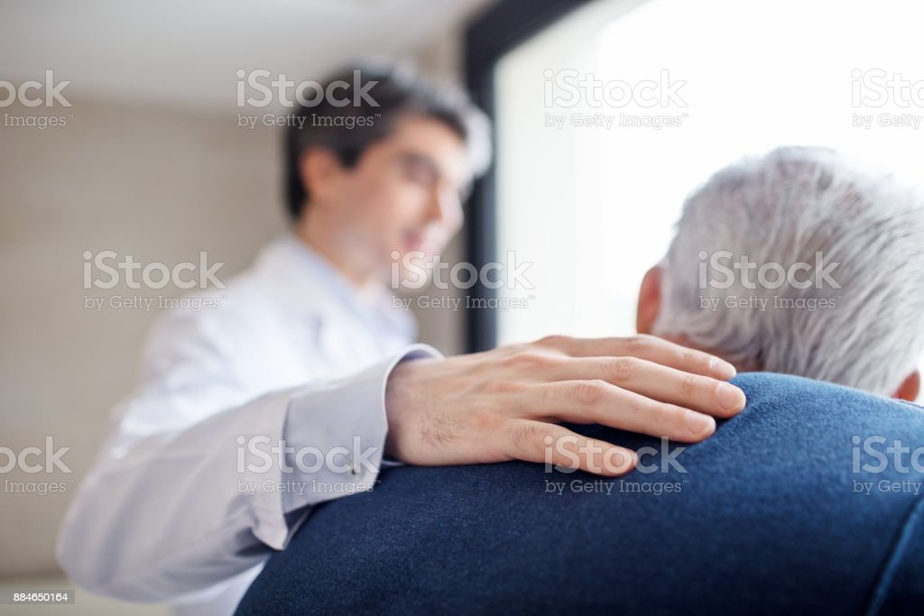 Doctor keeping hand on senior man's back royalty-free stock photo
