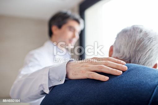 Close-up of doctor keeping hand on senior man's back. Male professional is showing care towards elderly patient. They are in hospital.