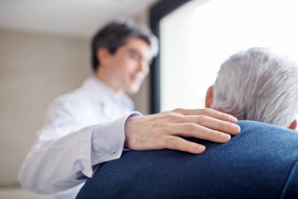 médico, manteniendo la mano sobre la espalda del hombre senior - atención de personas mayores fotografías e imágenes de stock