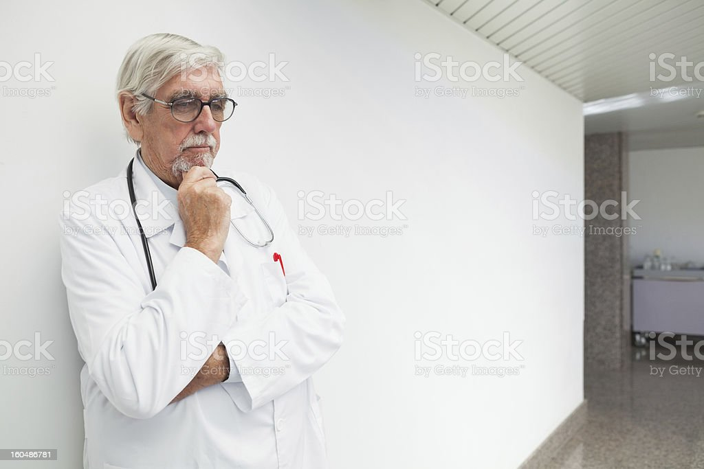 Doctor leaning against wall in corridor and thinking royalty-free stock photo