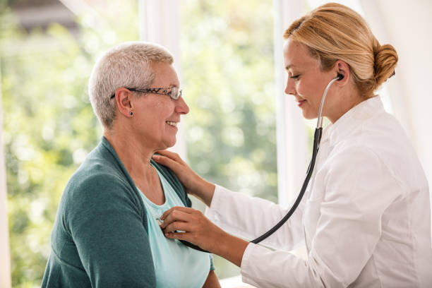Doctor listening patient's heartbeat stock photo