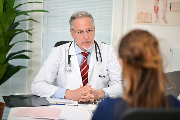 Doctor listening to his patient stock photo