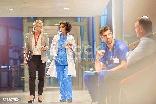 istock doctor listening to sales rep in hospital corridor 891807504