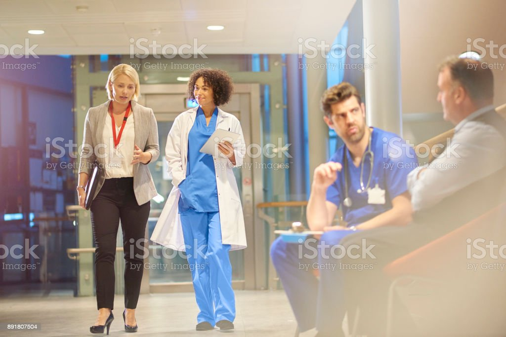 doctor listening to sales rep in hospital corridor stock photo