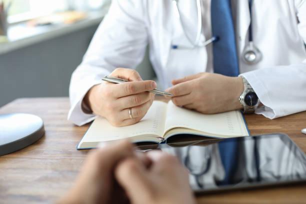 Arzt hört dem Patienten zu, während er von seinen Problemen erzählt. Männlicher Arzt, der Notizen macht. Hände nur über den Tisch. – Foto