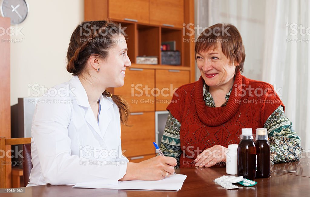 doctor listening woman at table stock photo