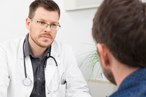 A doctor listens to his patient stock photo