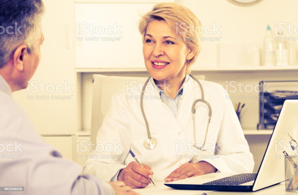 Médico ouve paciente maduro - Foto de stock de Adulto royalty-free