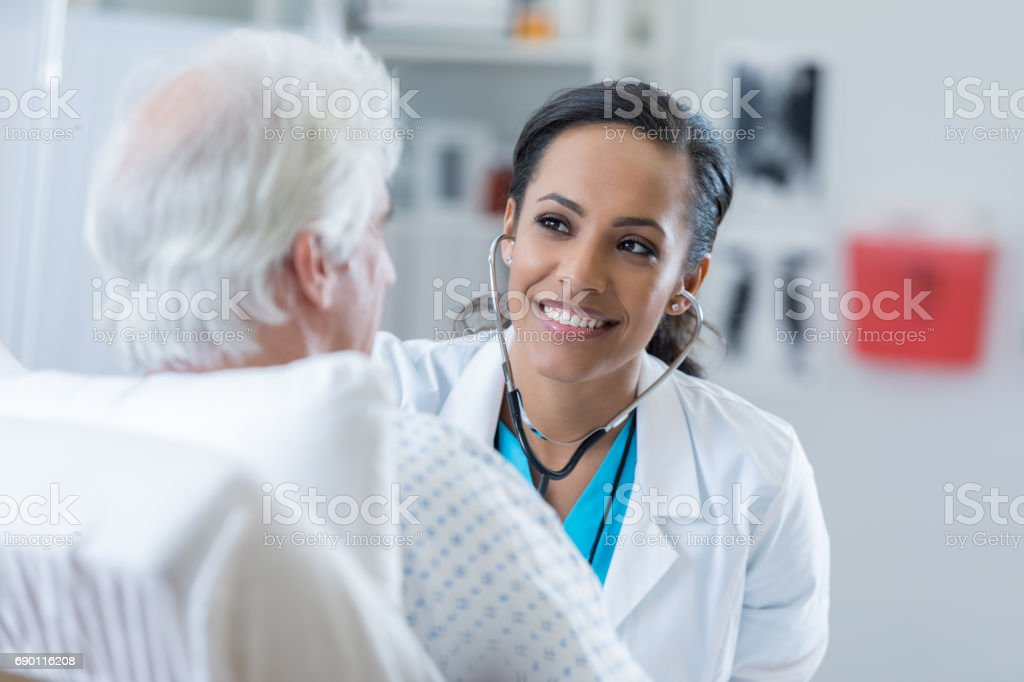 Doctor listens to patient's heart in the hospital stock photo