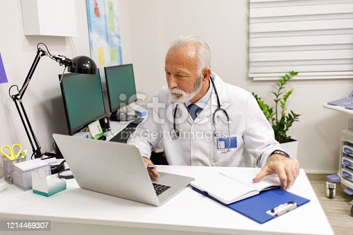 Doctor looking at medical charts on laptop