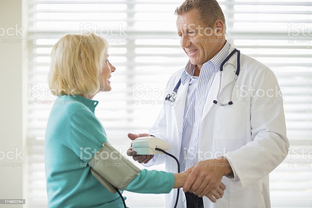 Doctor Looking At Patient While Examining Blood Pressure royalty-free stock photo