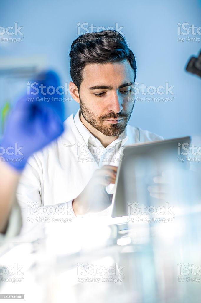 doctor looking   findings on a tablet in the lab stock photo