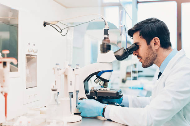 Doctor looking through a microscope stock photo