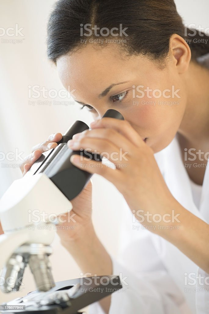 Doctor Looking Through Microscope In Laboratory royalty-free stock photo