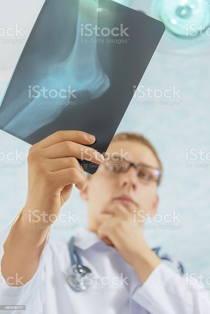 Doctor looks at x-ray image of knee joint stock photo
