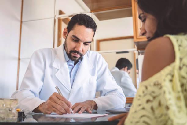 Arzt macht Verschreibung für weibliche Patienten – Foto