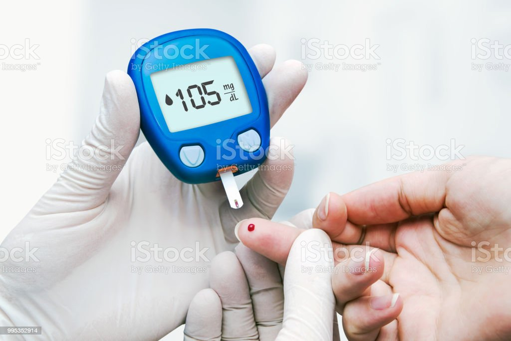 Doctor making blood sugar test in clinic for diabetes stock photo