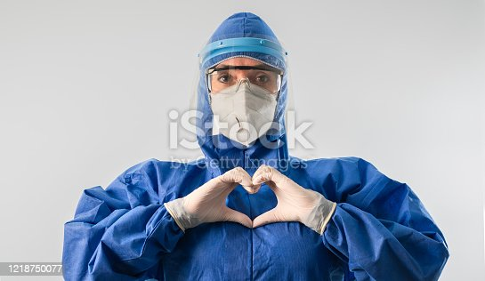 Healthcare worker woman wearing highly protective suit, making heart shape and motivating.