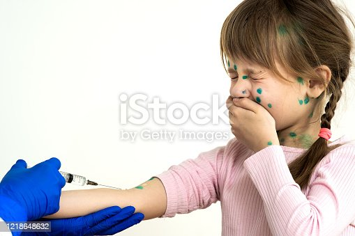 857285148 istock photo Doctor making vaccination injection to an afraid child girl sick with chickenpox, measles or rubella virus. Vaccination of children at school concept. 1218648632