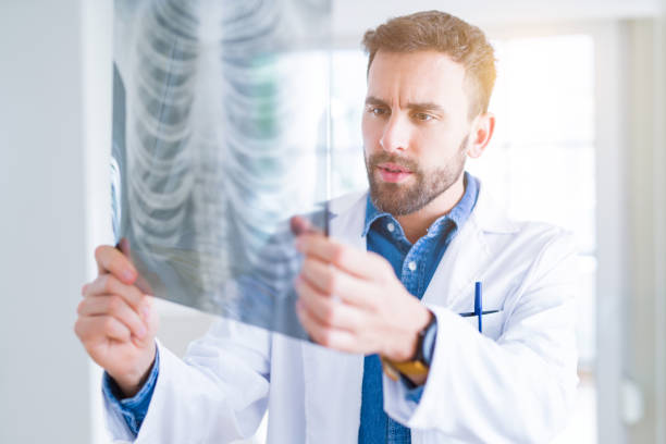 Doctor man looking at x-ray radiography doing body examination Doctor man looking at x-ray radiography doing body examination human rib cage stock pictures, royalty-free photos & images