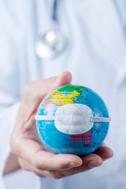 doctor man showing a globe with a mask stock photo