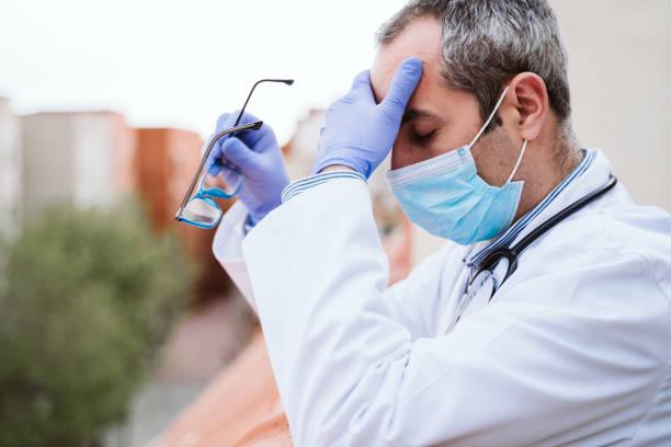médico tomando un descanso, con aspecto cansado, agotado o triste. Usar guantes protectores, máscara y estetoscopio. coronavirus cóvidio-19 concepto - foto de stock