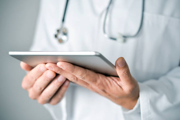 doctor man using a tablet computer - telemedicine stock pictures, royalty-free photos & images