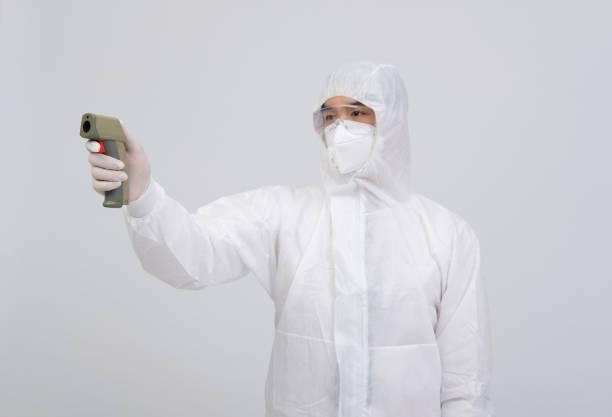 Arzt Mann trägt biologische Schutzuniform Anzug Kleidung, Maske, Handschuhe Messen Körpertemperatur mit Infrarot-Stirnthermometer – Foto