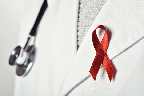 doctor man with a red ribbon closeup of a young caucasian doctor man with a pink ribbon pinned in the flap of his white coat, in solidarity of people living with HIV/AIDS hiv stock pictures, royalty-free photos & images
